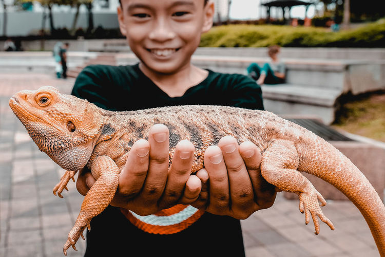 Smiling Boy Holding Lizard While Standing Outdoors