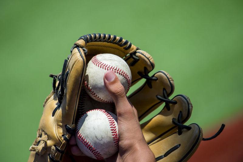 Cropped hand holding baseball ball