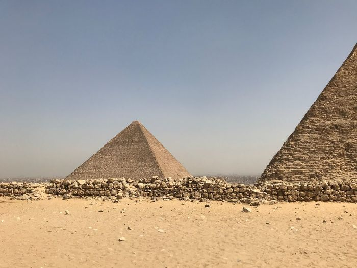 Pyramids on sand against clear sky