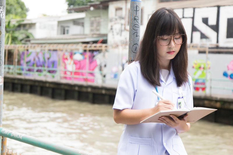 Female Doctor Writing In Book While Standing Outdoors