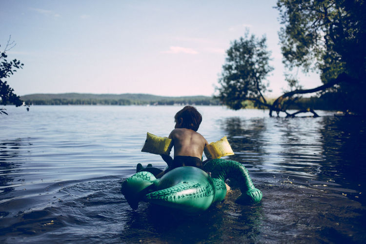 Boy swimming with air filled toy crocodile Filled Swimming Air Boy Child Crocodile Day Lake Leisure Activity Lifestyles Nature One Person Outdoors People Plastic Real People Sitting Toy Tree Water Waterfront