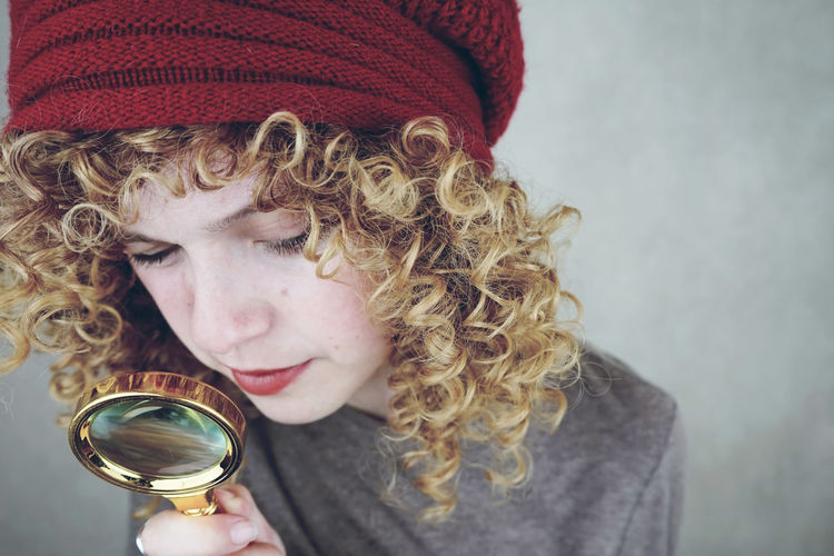 Close-Up Of Young Woman Looking Through Magnifying Glass Against Gray Background