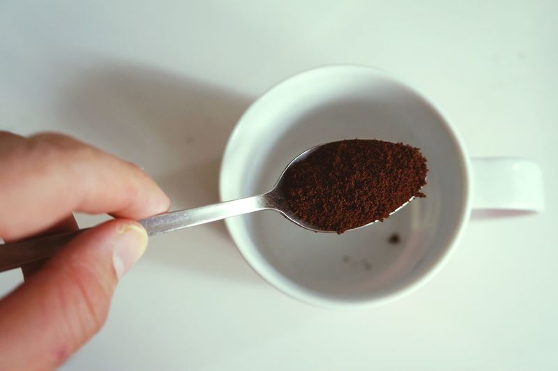 Cropped Hand Holding Spoon With Ground Coffee Above Coffee Cup On Table