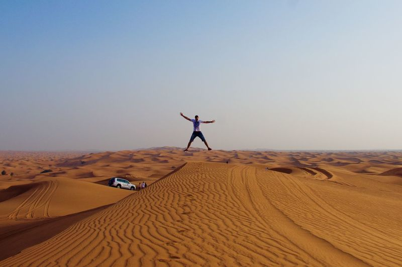 Man with arms outstretched jumping on desert against sky during sunset
