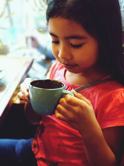 Girl Holding Coffee Cup While Sitting At Cafe