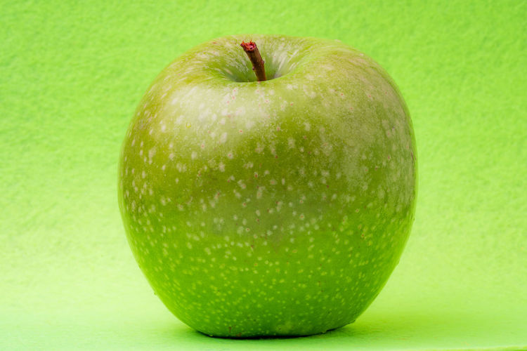 Close-up of apple against green background