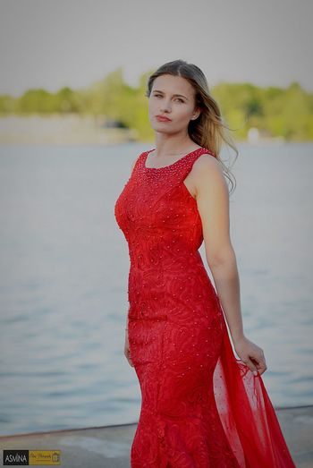 Portrait of beautiful young woman standing wearing red dress outdoors