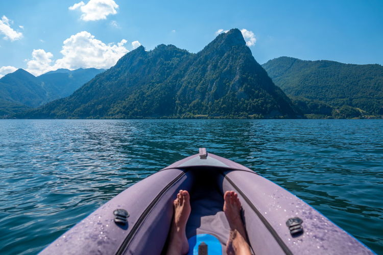 Man in boat on lake against mountains
