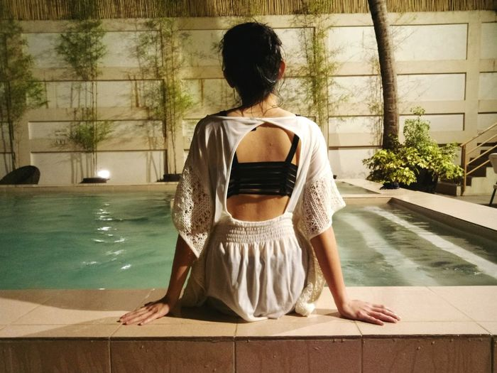 Rear View Of Woman Sitting At Poolside