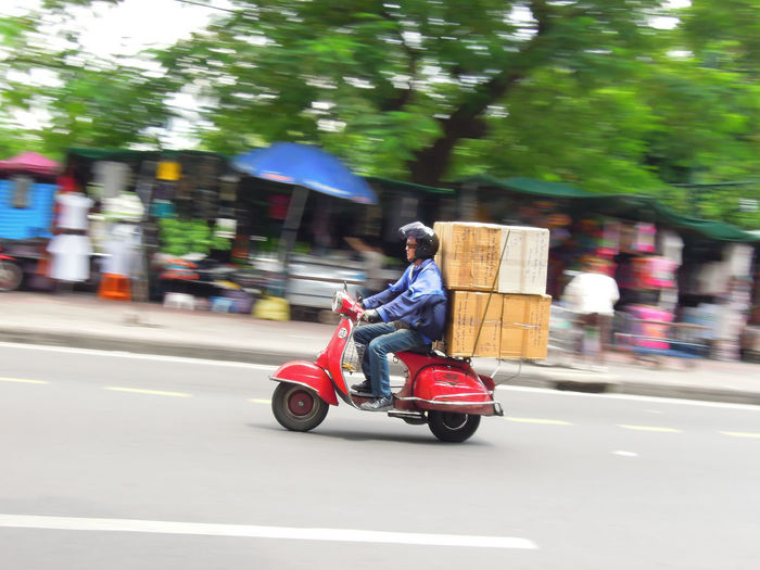 Side view of man riding motor scooter on roadside