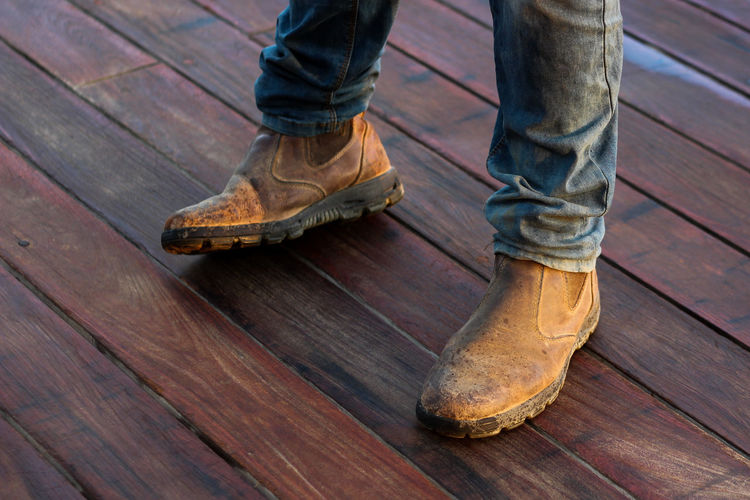 Low section of man standing on wooden floor