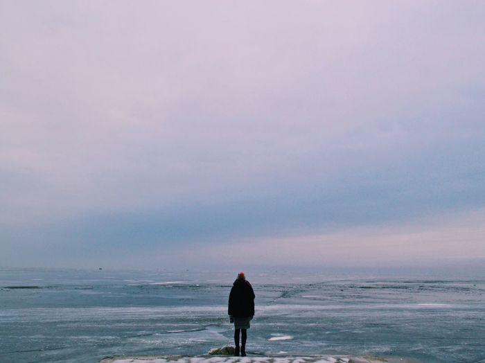 Woman Standing On Seashore In Winter
