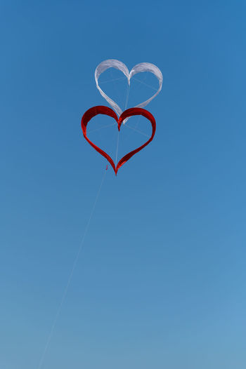 Low angle view of heart shape against clear blue sky
