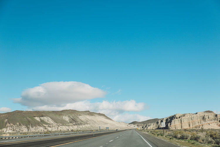 Road by mountains against blue sky