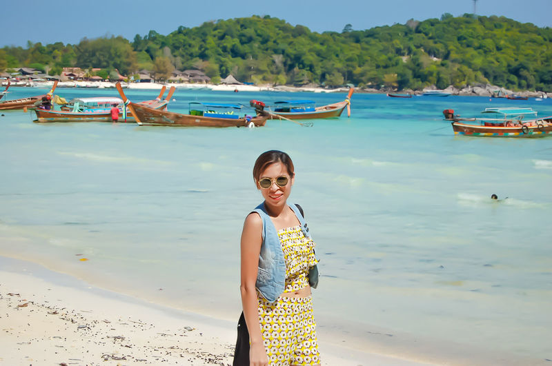 Portrait of woman in sunglasses standing at beach