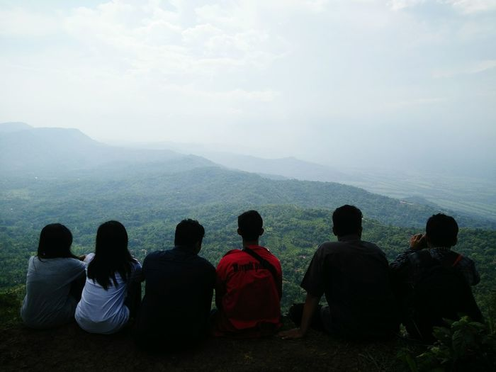 Rear view of friends sitting on hill against sky