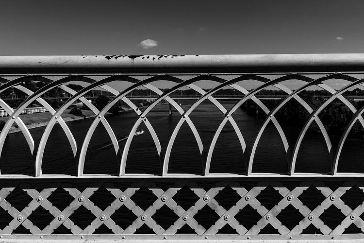 Birds on bridge against sky