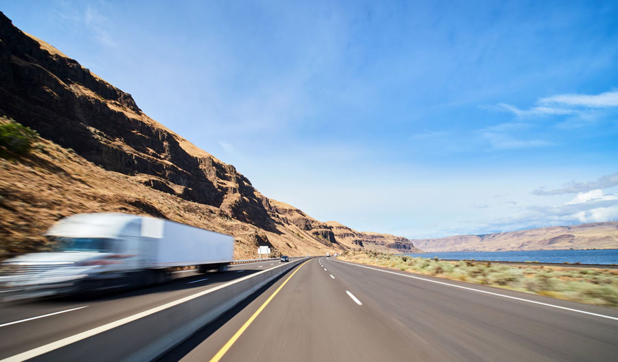 Transportation Road Mountain Sky Land Vehicle Mode Of Transportation Motion Symbol Marking Road Marking Motor Vehicle Sign Car Nature No People Cloud - Sky The Way Forward Day Direction Blurred Motion Mountain Range Outdoors Diminishing Perspective Road Trip Dividing Line