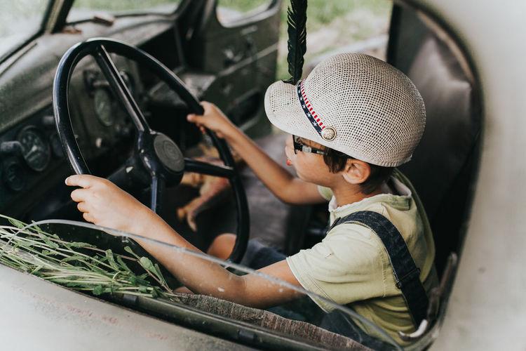 Boy holding steering wheel sitting in car