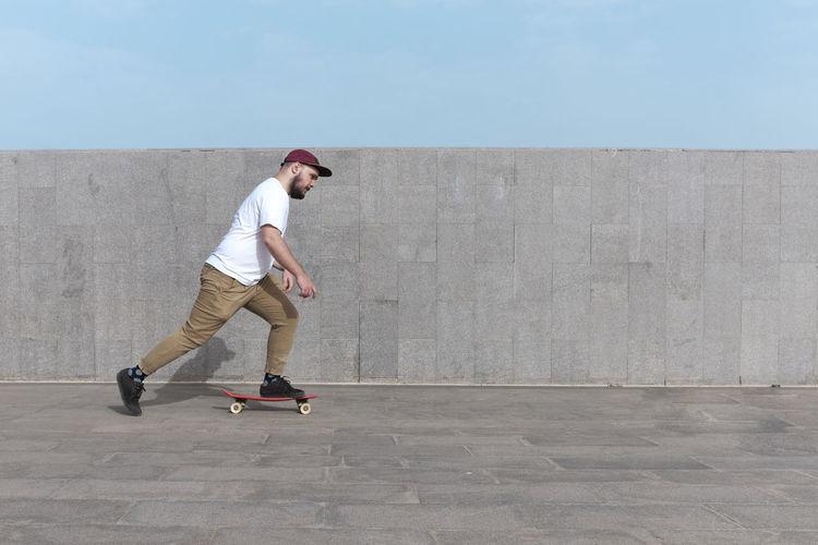 Full length side view of man skateboarding on wall against sky
