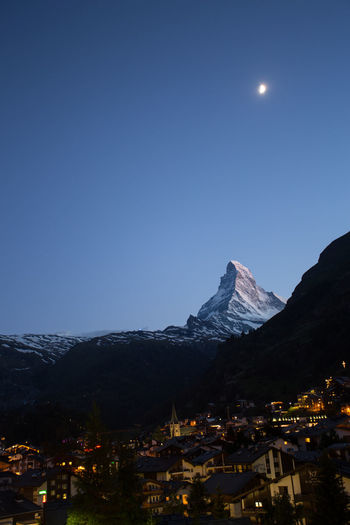 The Matterhorn, Zermatt, Switzerland illuminated by the moon with the lights of the town in the valley. Matterhorn  Architecture Beauty In Nature Building Building Exterior Built Structure City Clear Sky Copy Space Dusk Illuminated Moon Moonlight Mountain Mountain Peak Mountain Range Nature Night No People Outdoors Scenics - Nature Sky Snowcapped Mountain Zermatt Switzerland