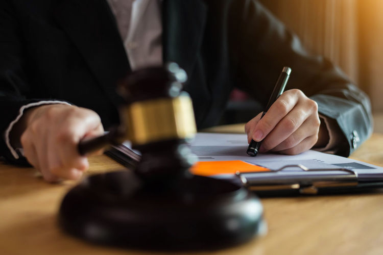 Midsection of lawyer holding gavel on desk in office