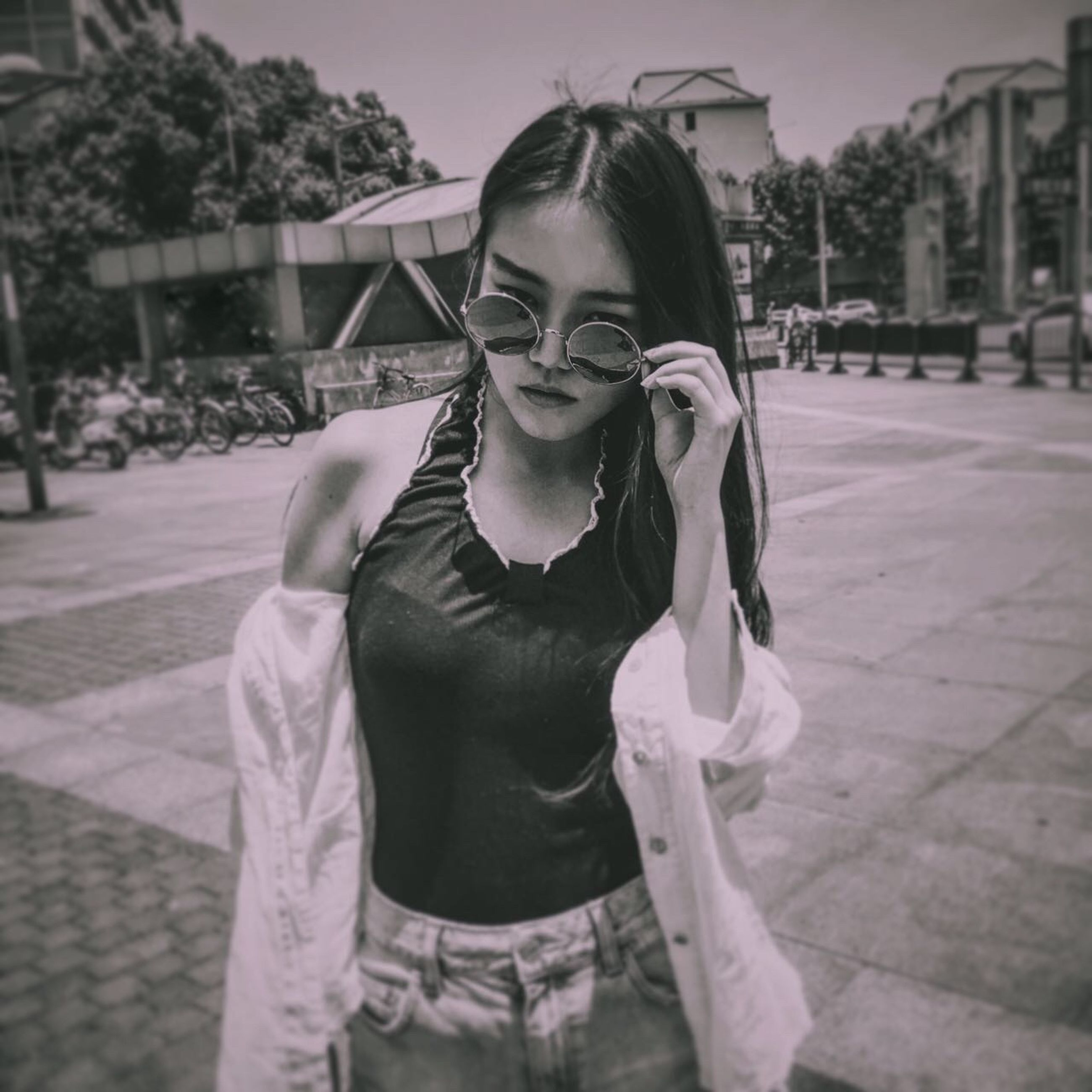 portrait, looking at camera, young adult, lifestyles, person, front view, casual clothing, sunglasses, leisure activity, standing, smiling, focus on foreground, young women, waist up, holding, fashion, outdoors, day