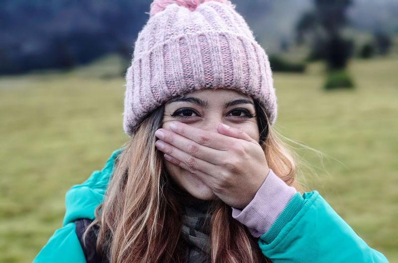 Close-Up Portrait Of Young Woman Covering Mouth On Field