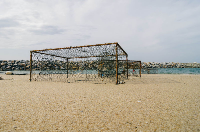 closeup rusty crab pots on the sandy beach white cloudy sky Beach Calm Chainlink Fence Cloud - Sky Crab Pots Day Nature Non-urban Scene Outdoors Protection Remote Safety Sand Scenics Sea Shore Sky Surface Level Tranquil Scene Tranquility Vacations Water