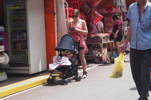 Architecture Baby Stroller Building Exterior Casual Clothing Childhood Day Full Length Leisure Activity Lifestyles Men Outdoors People Real People Retail  Sitting Supermarket Togetherness Transportation Women