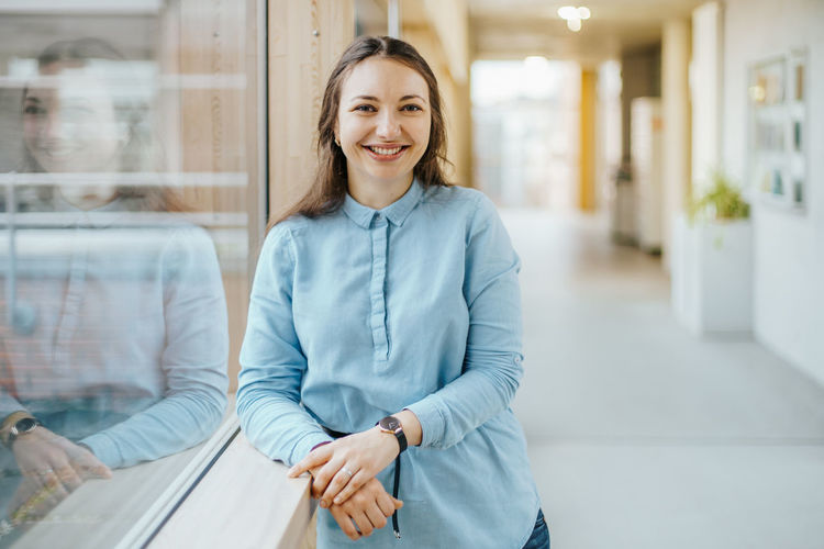 smiling caucasian businesswoman wearing a blue blouse leanaing against window Smiling Looking At Camera Portrait Happiness Business Confidence  Business Person Adult One Person Emotion Women Three Quarter Length Young Adult Indoors  Brown Hair Focus On Foreground Window Office Hairstyle Office Hallway Cheerful Caucasian Professional Brunette