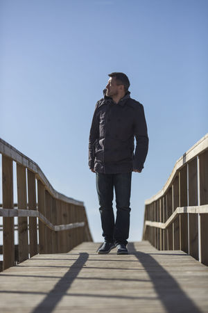 Man walking on boardwalk toward the camera. 45-50 Heroic Masculinity Blue Boardwalk Casual Clothing Clear Sky Day Detective Direction Front View Full Length Leisure Activity Lifestyles One Person Outdoors Real People Shadow Sky Sunlight Thriller Tough Walking Young Adult