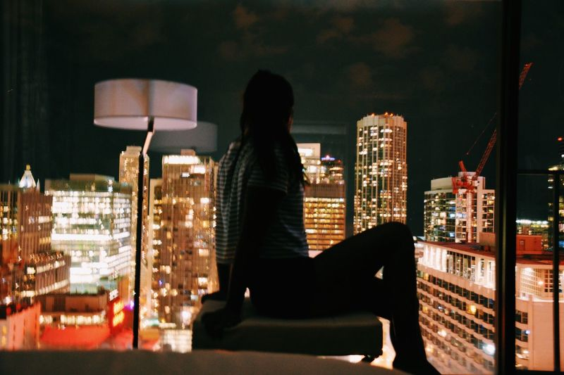 Woman On Seat Looking At Illuminated Buildings Seen Through Window During Night