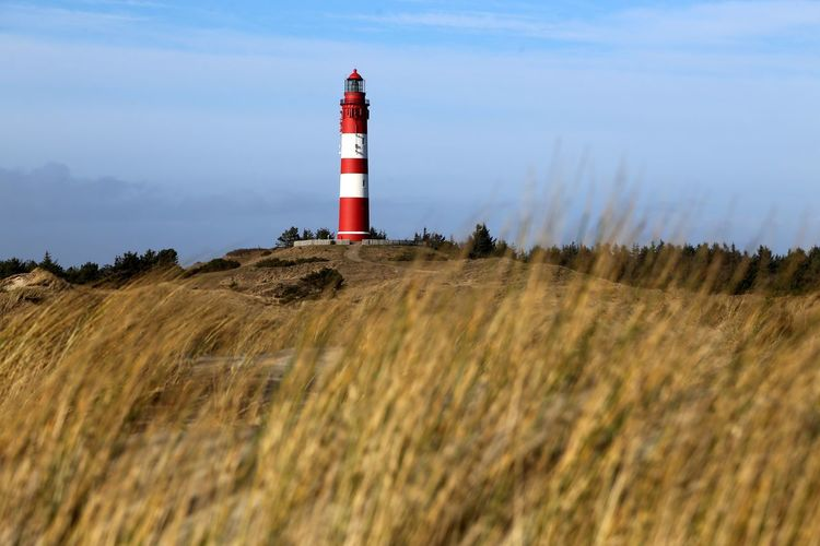 Lighthouse on landscape against sky