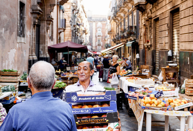 A man carries fruit boxes at the market in Palermo Food And Drink Retail  Market Healthy Eating Travel Destinations City Street Streetphotography Street Photography Palermo Sicily Wearing Smile Alley Old Town Vegetables Fruits