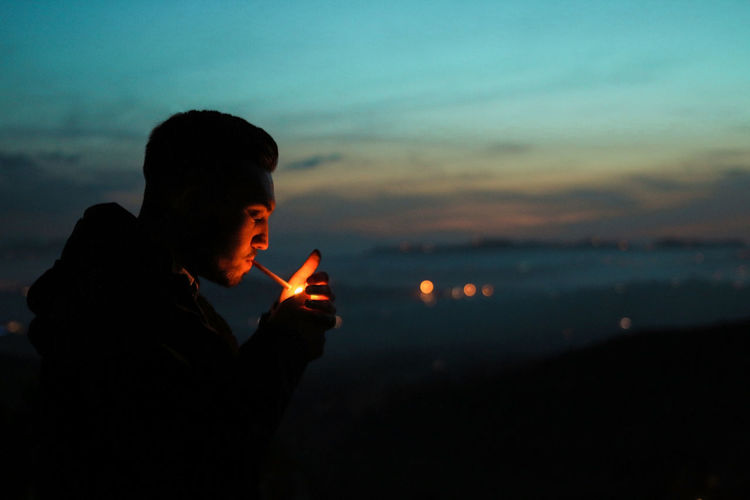 Side view of silhouette man smoking cigarette against sky at dusk