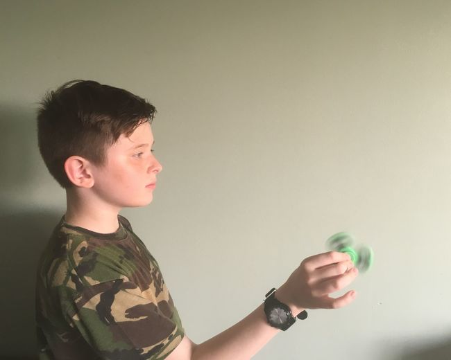 Side view of boy playing with spinner against wall at home