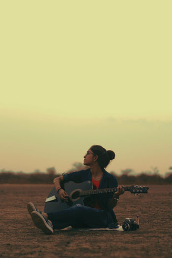 Young woman playing guitar while sitting on field against sky