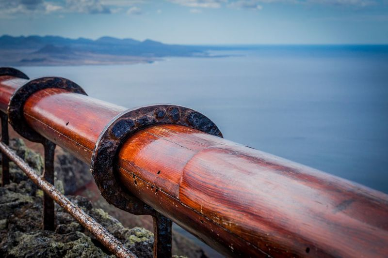 Close-up of rusty pipe by sea against sky