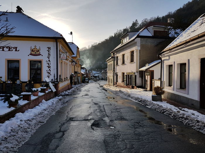 Street amidst buildings against sky during winter