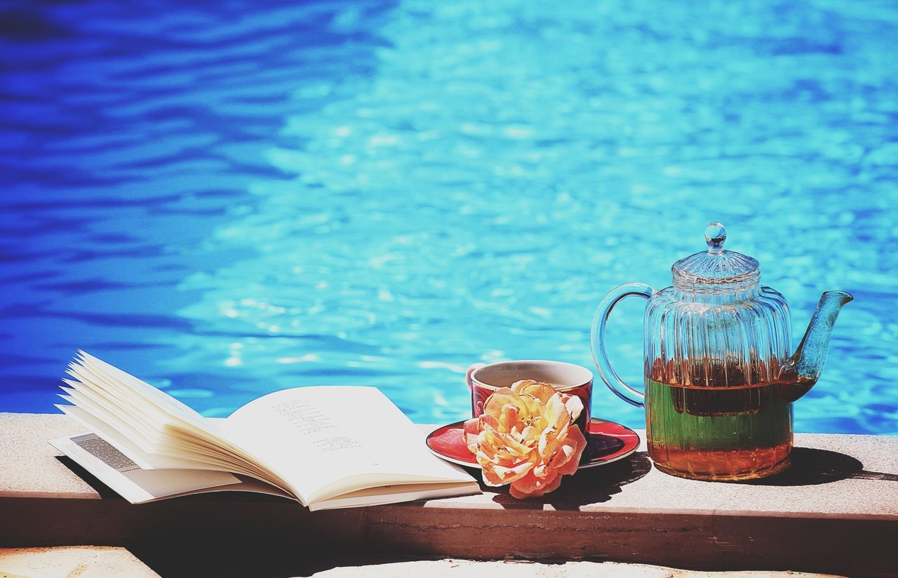 Book With Tea And Kettle By Swimming Pool