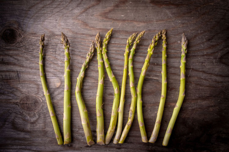 Raw freshly picked asparagus Food And Drink Green Asparagus Close-up Directly Above Food Food And Drink Foodphotography Freshness Green Color Group Of Objects Healthy Eating High Angle View In A Row Indoors  Large Group Of Objects No People Raw Food Season  Still Life Studio Shot Table Vegetable Wellbeing Wood - Material Wood Grain