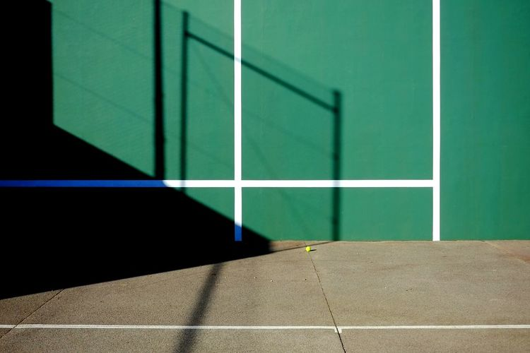 Shadow on green wall at tennis court