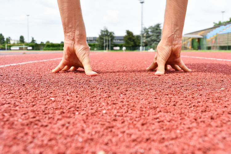 Cropped hands of man on sports track