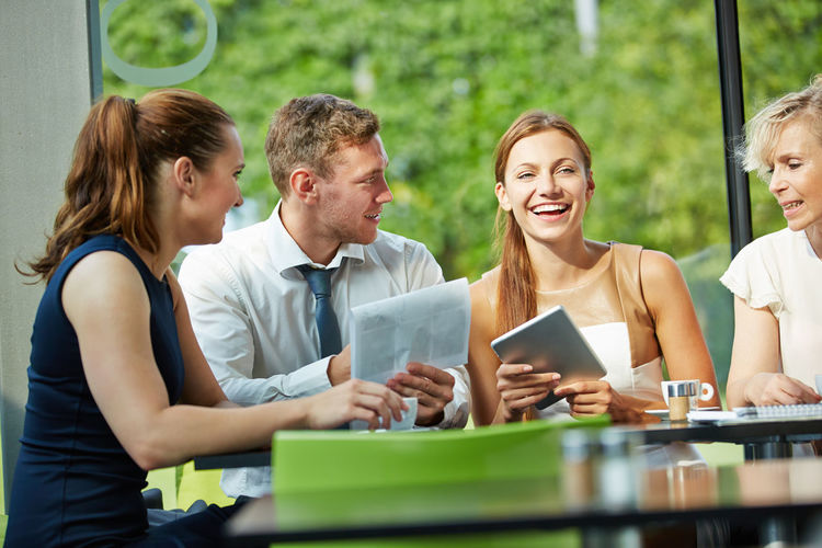 Cheerful Business People Sitting At Table Outdoors