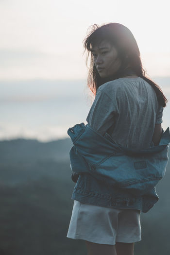 Portrait of lonely Asian woman with jean jacket is spacing out and standing at mountain peak in morning with the camera. Alone Sea Of ​​clouds Feeling Film Fog Hurt Journey Landscape Leisure Lonely Mountain Nature Outdoors Passion Rim Light Travel Unhappy Vacations View Warm Jeans Adult Mist Freedom Standing