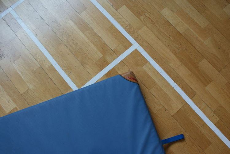 High angle view of mattress on hardwood floor at home