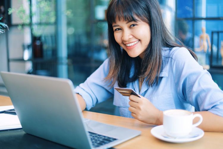 Portrait of smiling businesswoman holding credit card in office