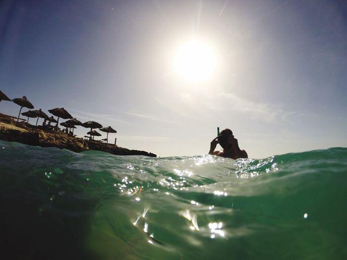Man snorkeling in sea against sky