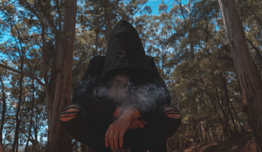 Low angle view of woman exhaling smoke while sitting against trees
